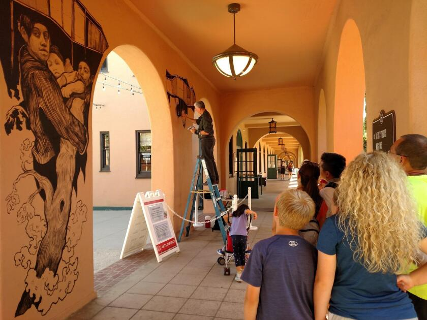 Passersby watch artist Hugo Crosthwaite work on a mural at Liberty Station in Point Loma last week.