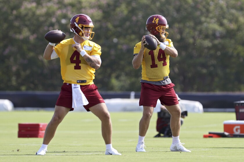 Washington Football Team quarterbacks Taylor Heinicke (4) and Ryan Fitzpatrick (14) throw passes during NFL football practice in Richmond, Va., Wednesday, July 28, 2021. (AP Photo/Ryan M. Kelly)