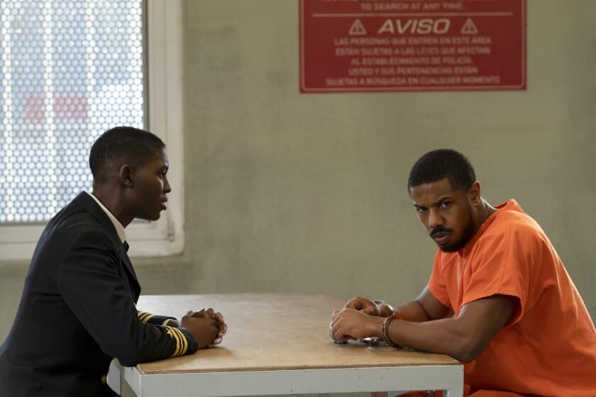 Jodie Turner-Smith and Michael B. Jordan sit across a table; Jordan wears a prison jumpsuit.