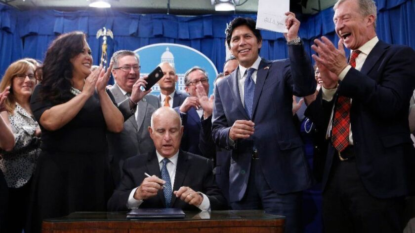 California lawmakers and others celebrate after Gov. Jerry Brown signed SB 100 in Sacramento on Monday, committing the state to 100% clean energy by 2045.