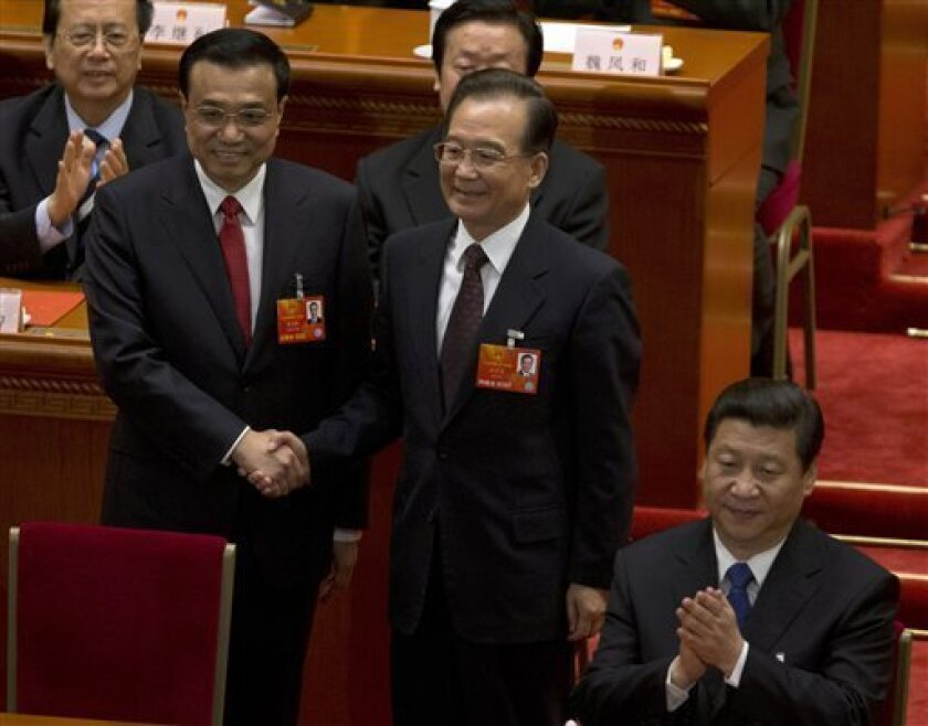 Newly named Chinese Premier Li Keqiang, left, shakes hands with former Chinese Premier Wen Jiabao near Chinese President Xi Jinping, right, during a plenary session of the National People's Congress where delegates voted Li as new premier at the Great Hall of the People in Beijing Friday, March 15, 2013. (AP Photo/Ng Han Guan)