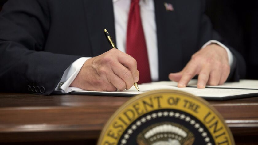 President Trump signs an executive order at the White House on Oct. 12 that critics say is intended to draw young and healthy consumers off the markets created by the Affordable Care Act.