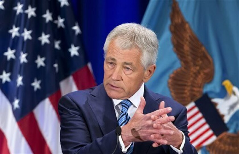 """FILE - In this April 3, 2013 file photo U.S. Defense Secretary Chuck Hagel speaks at the National Defense University in Fort McNair, Washington. Hagel said the greatest financial threat to the Pentagon isn't budget cuts but rather the """"unchecked, spiraling costs"""" of new weapons and personnel benefits. He warned of sharply deeper cuts to personnel, health care and weapons systems across his department, and next week's budget blueprint is expected to include several congressionally unpopular propo"""