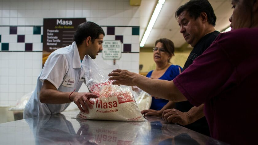 Grocery store clerk Hector Esparza hands out masa to customers at Amapola Market in Downey. Last Christmas, numerous customers returned masa purchased at Amapola seeking refunds.