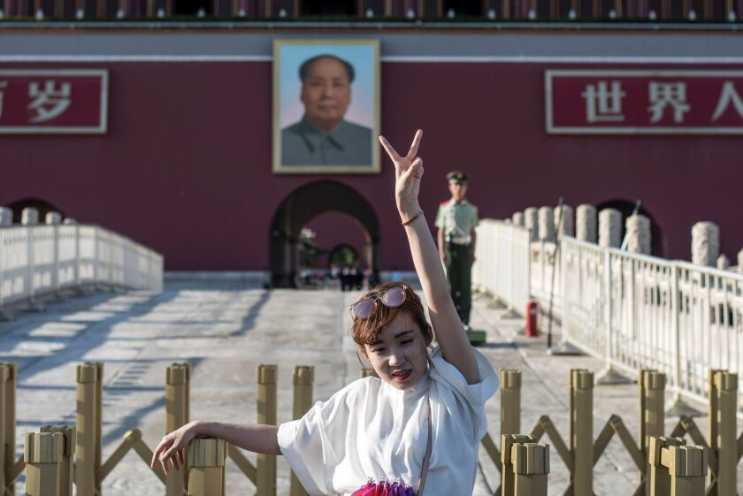 A tourist poses in front of a giant portrait of Mao Tse-Tung at the gate of the Forbidden City in Beijing on May 16, 2016. Official Chinese media stayed largely silent about the 50th anniversary of the start of the bloody Cultural Revolution, and discussion of the tumultuous decade is still controlled on the mainland.