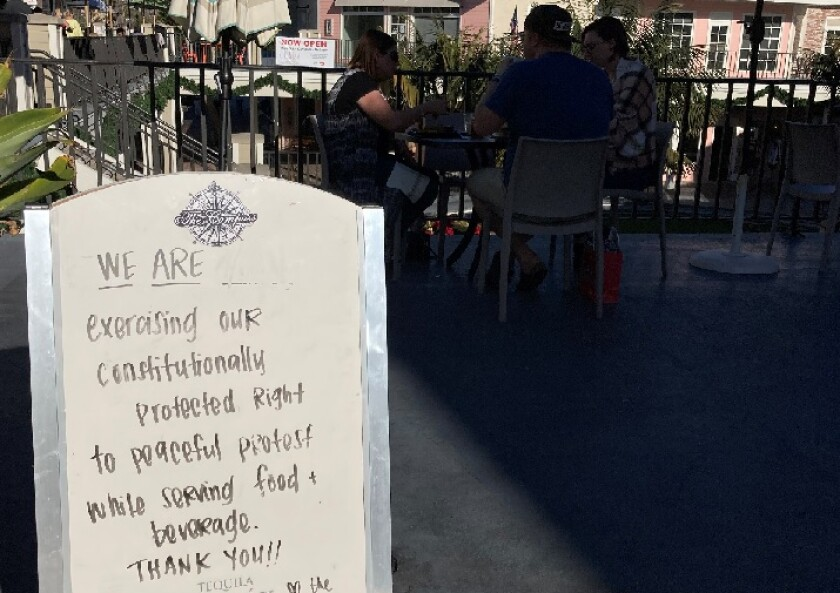 """A sign outside The Compass in Carlsbad says the restaurant is open as a """"peaceful protest"""" of county health orders."""