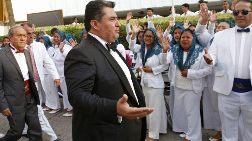 En esta foto del 14 de agosto de 2018, Naasón Joaquín García saluda a los miembros de su iglesia, La Luz del Mundo, en Guadalajara, México. García está acusado de tráfico de personas y violación de menores, informaron las autoridades de California el martes. (AP)