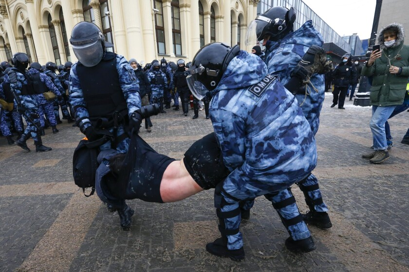 Police carry away a protester in Moscow.