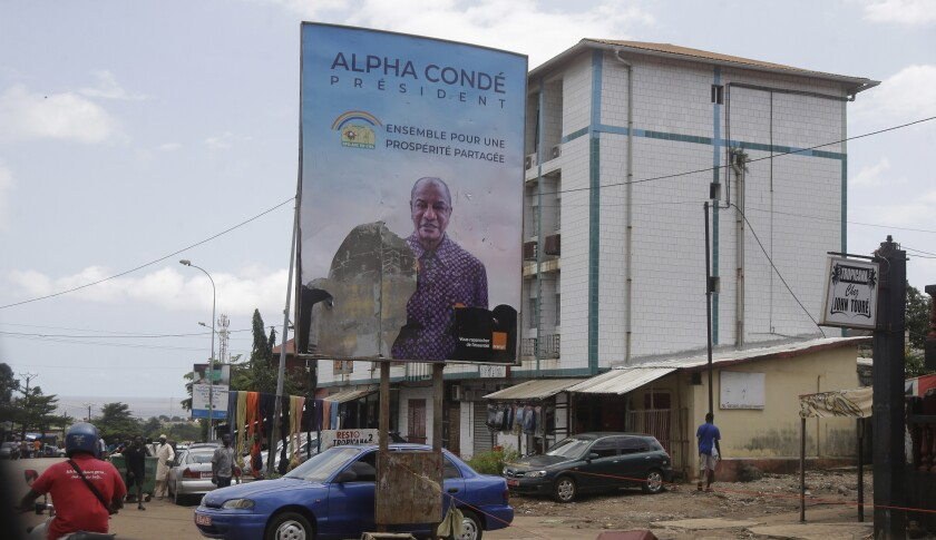People walk past a defaced billboard with former Guinea's President Alpha Conde, on a street in Conakry, Guinea, Thursday, Sept. 9, 2021. Guinea's new military leaders sought to tighten their grip on power after overthrowing President Alpha Conde, warning local officials that refusing to appear at a meeting convened Monday would be considered an act of rebellion against the junta. (AP Photo/Sunday Alamba)
