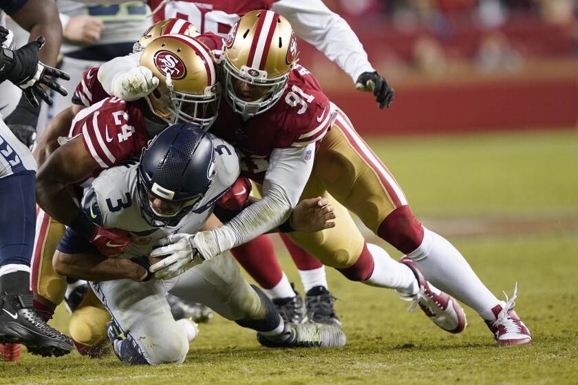 Seattle Seahawks quarterback Russell Wilson, bottom, is tackled under San Francisco 49ers defensive back K'Waun Williams (24) and defensive end Arik Armstead (91) during a game in Santa Clara on Nov. 11.