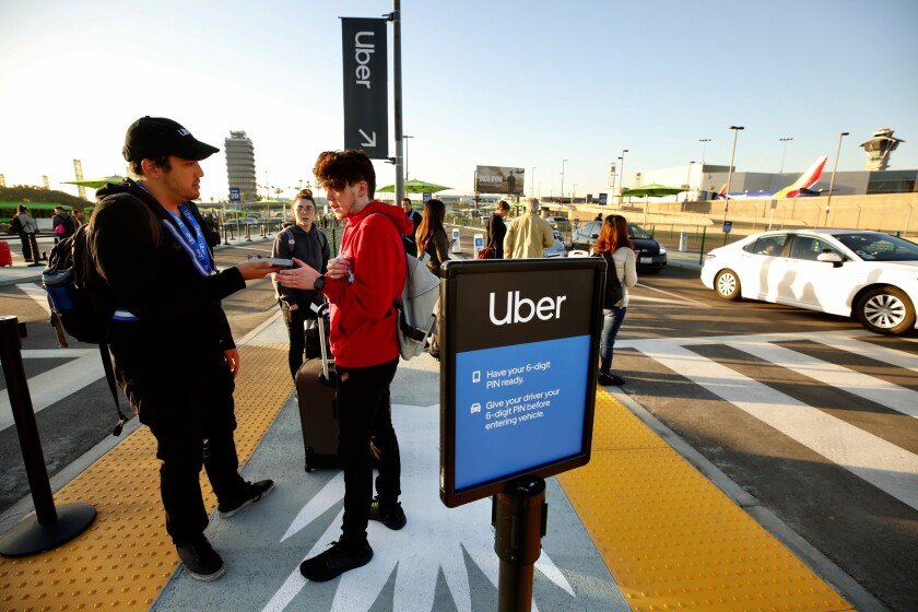 Alex Geddo left, with Uber, helps passenger Kaleb Brewer, arriving from Oklahoma, at the new LAX passenger pickup lot on Oct. 29, the first day of the new ride-hailing change.