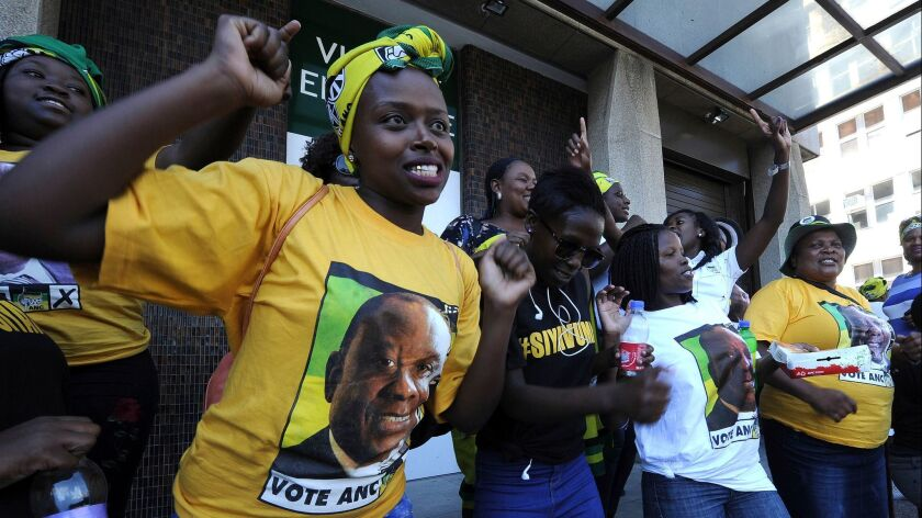 Supporters for president elect Cyril Ramaphosa, portrait on t-shirt, sing and dance outside in Cape Town, South Africa, on Feb 15.
