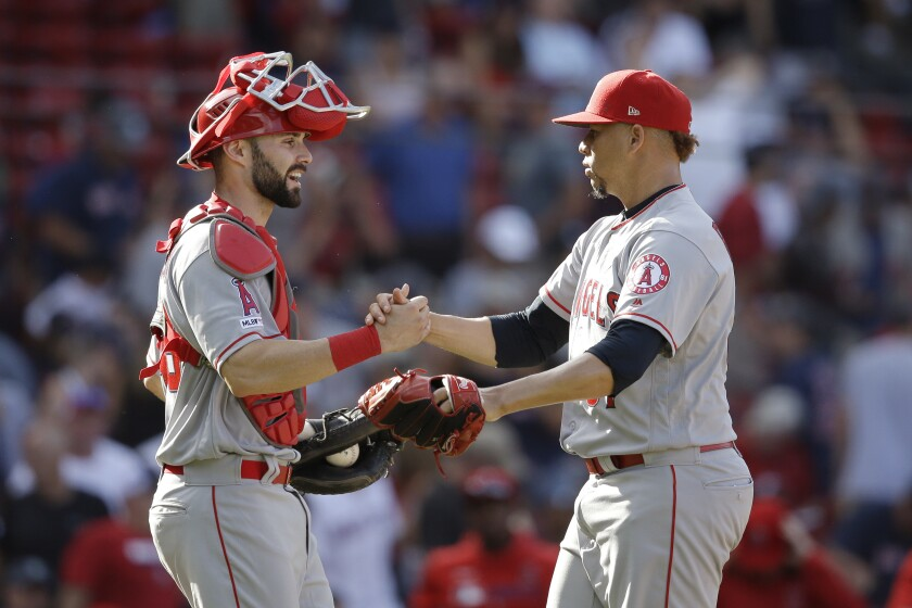 Angels' Max Stassi, left, and Hansel Robles celebrate their win over the Boston Red Sox on Aug. 11 in Boston.