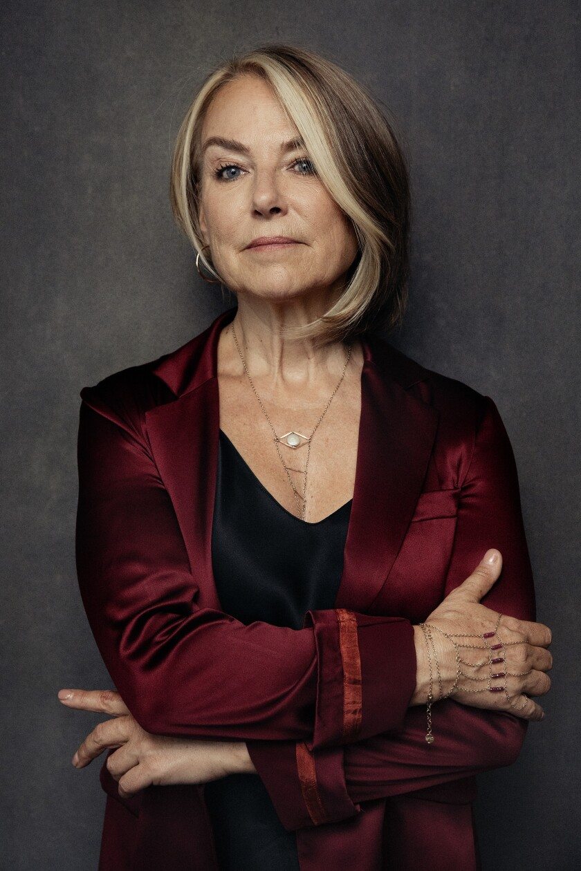 A woman in a maroon jacket crosses her arms