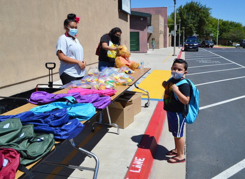 Second grader J.C. Solano picks up his new backpack from Valley ASES team members Kayla Long and Andrea Martinez.