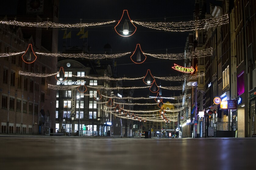 The deserted Damrak street is seen during curfew in the heart of Amsterdam, Saturday, Jan. 23, 2021. The Netherlands entered its toughest phase of anti-coronavirus restrictions to date, imposing a nationwide night-time curfew from 9 p.m. until 4:30 a.m. in a bid to control the COVID-19 infection rate. (AP Photo/Peter Dejong)