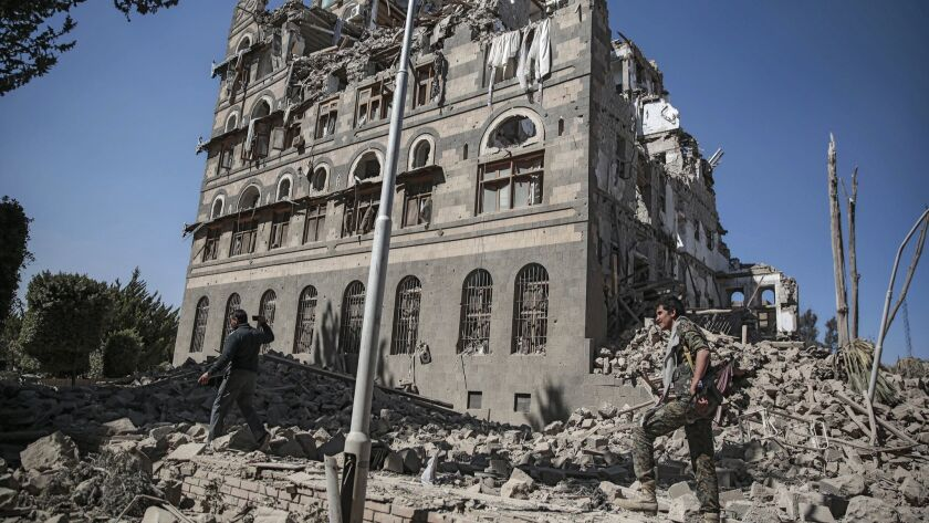 FILE - In this Dec. 6, 2017 file photo, Houthi Shiite rebels inspect the rubble of the Republican Pa