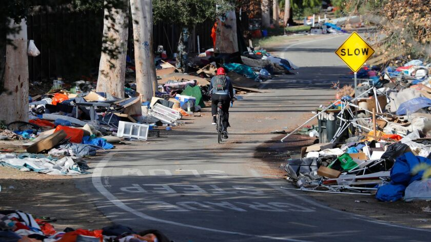 A bicyclist rides past piles of trash from the Santa Ana River homeless camp after it was cleared and more than 700 people relocated in Anaheim in February.