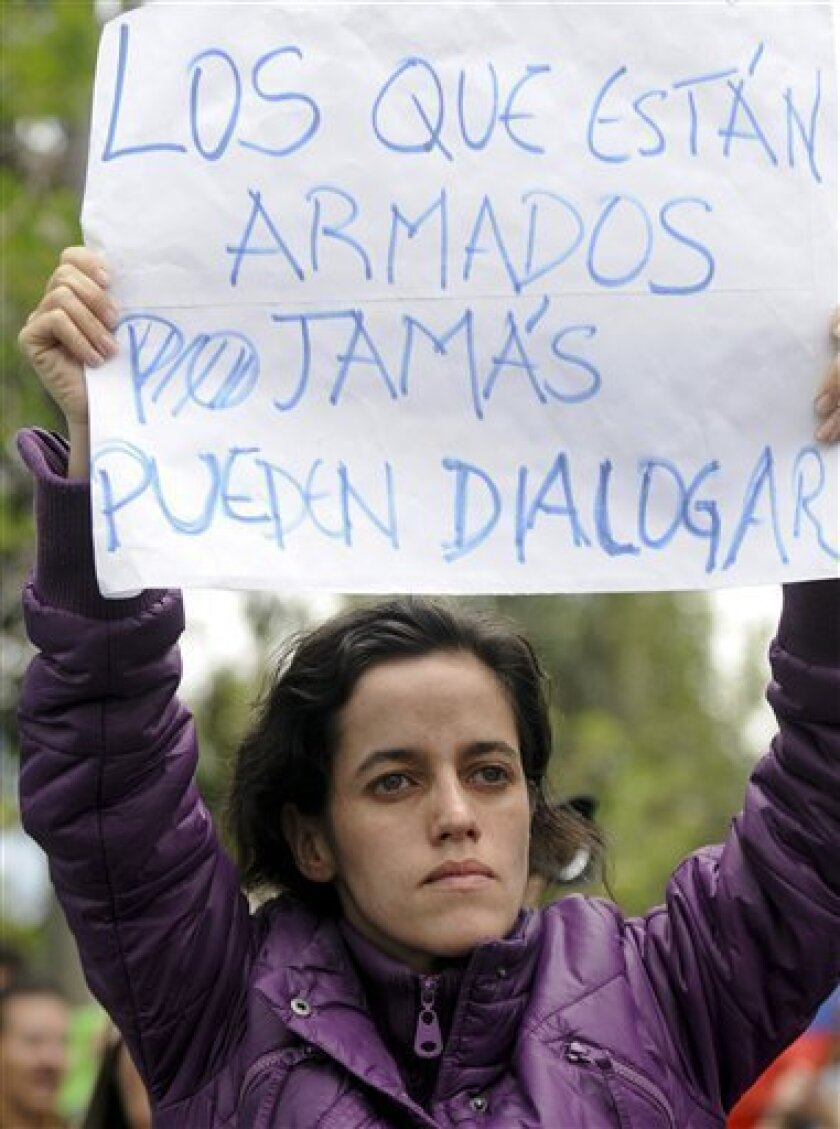 """A woman protests against rebellious police as she holds a sign that reads in Spanish """"Those who are armed can never talk"""" outside the hospital where Ecuador's President Rafael Correa is located in Quito, Ecuador, Thursday Sept. 30, 2010.  The government declared a state of siege Thursday after rebe"""