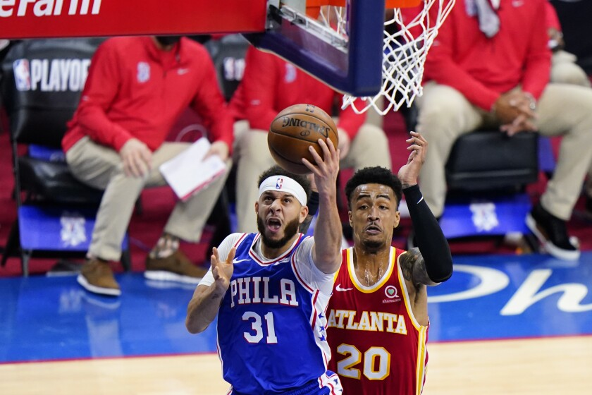 Philadelphia 76ers' Seth Curry, left, goes up for a shot past Atlanta Hawks' John Collins during the first half of Game 2 in a second-round NBA basketball playoff series, Tuesday, June 8, 2021, in Philadelphia. (AP Photo/Matt Slocum)