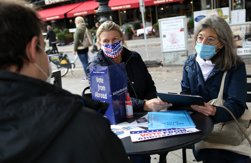 In Berlin, Florian Schiedhelm, from left, and Renee Johnsson help Emily Schalk to register for absentee vote in U.S. election