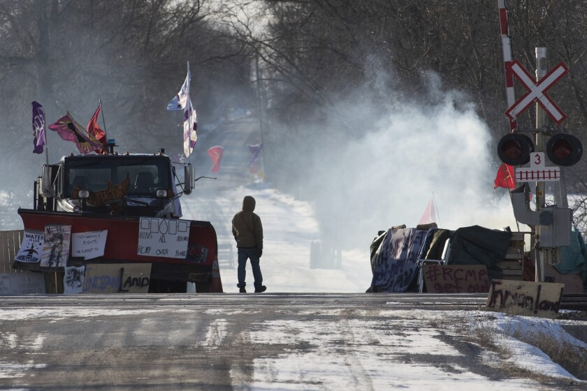 A protester stands at closed train tracks amid smoke, signs and a parked snowplow.