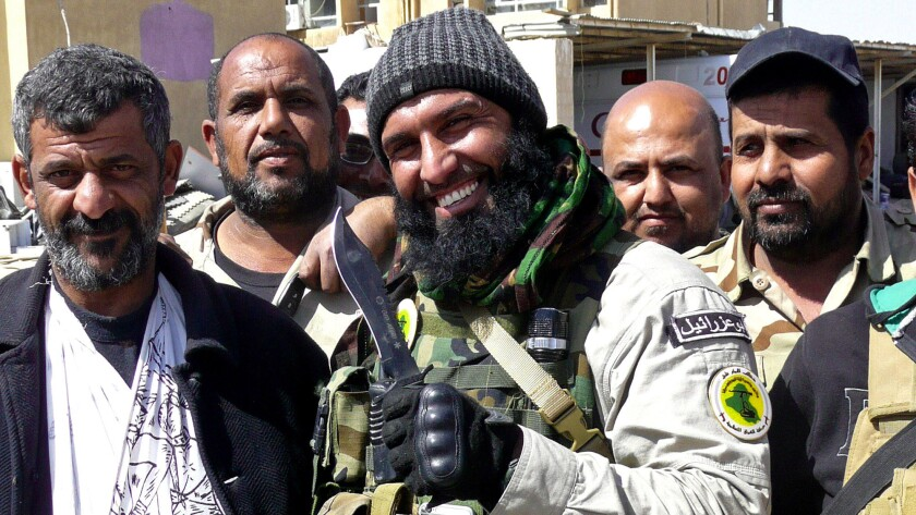 Abu Azrael, center, a hero among Shiite militiamen, poses with fighters near the northern Iraqi city of Tikrit on March 14, 2015.