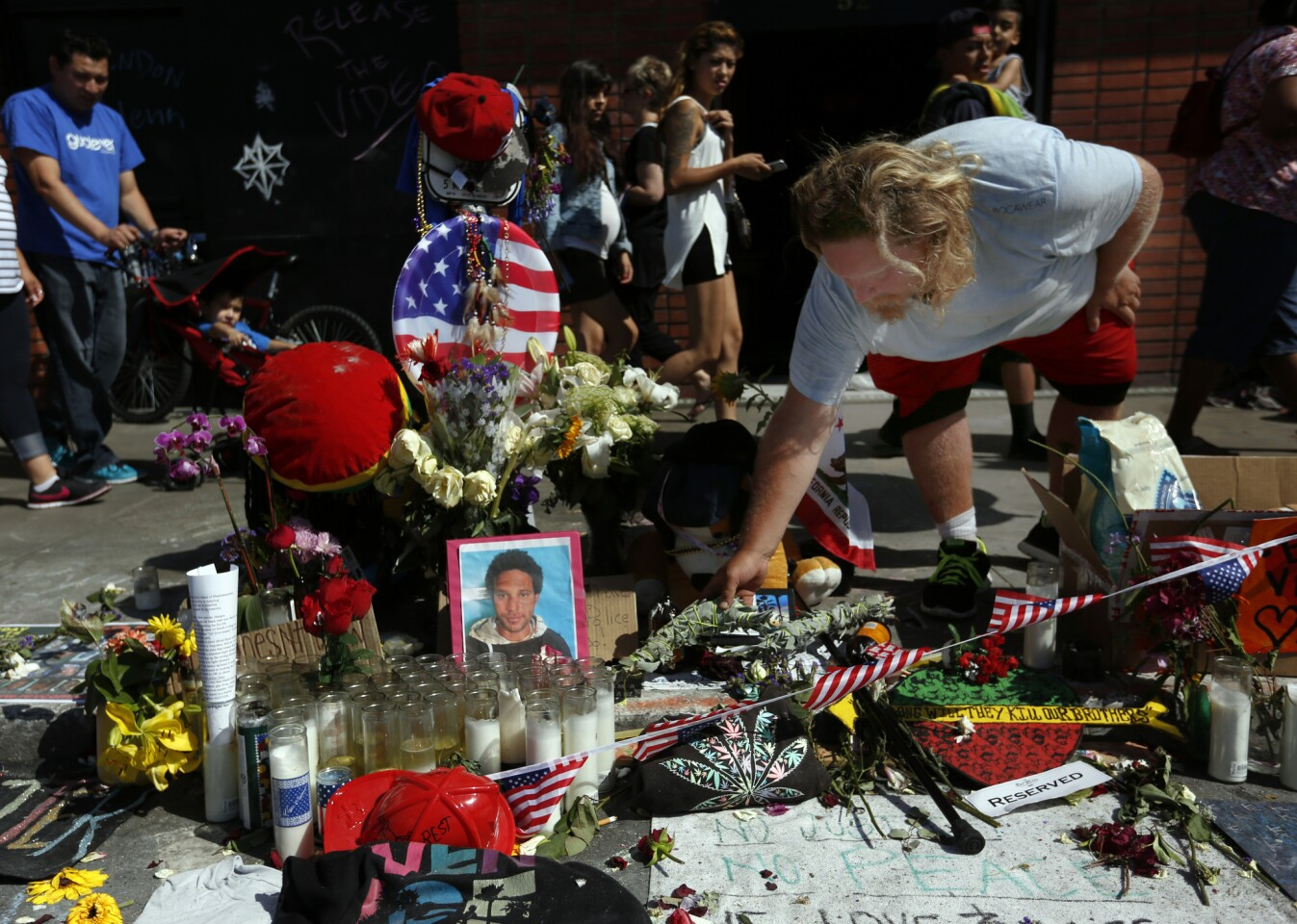 Bruce Chartier, 30, places sage on a memorial for his friend Brendon Glenn in Venice.