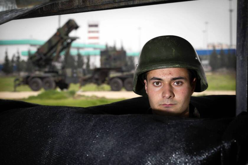 A Turkish soldier in a dugout guards a Patriot missile defense system, background, at an airbase in Adana, Turkey.