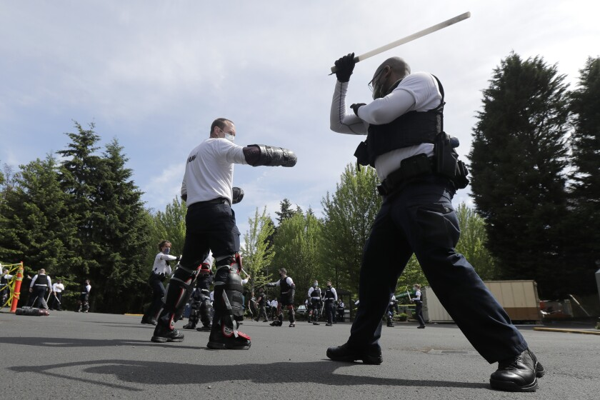 In this June 4, 2020, photo, law enforcement officers at the Washington state Criminal Justice Training Commission training facility in Burien, Wash., take part in a class on the use of batons as part of the more than 700 hours of training police and other officers are required to to through in the state of Washington. Police training has been under scrutiny again since the death of George Floyd, a black man who died after being restrained by Minneapolis police officers. (AP Photo/Ted S. Warren)