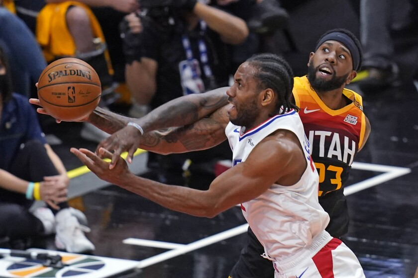 Clippers forward Kawhi Leonard is fouled by Jazz forward Royce O'Neale on a drive to the basket.