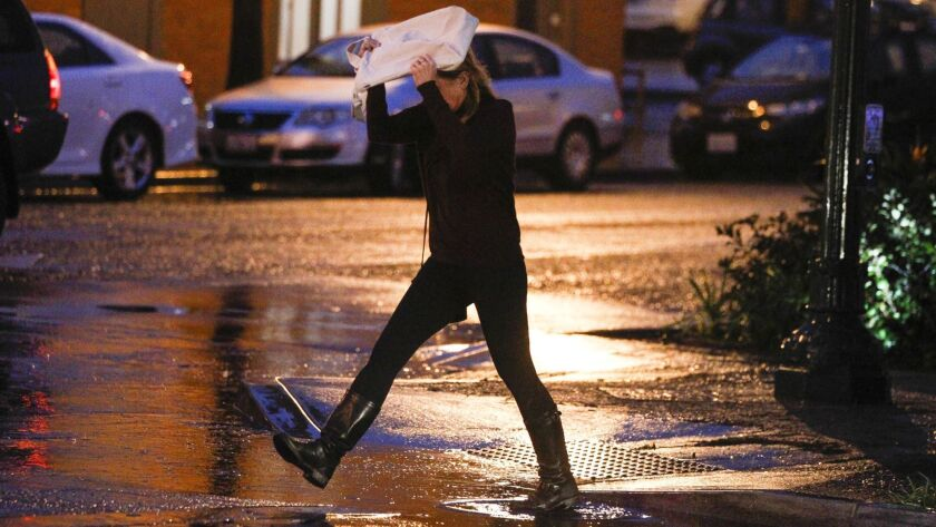 Rebecca Bray steps off the curb as she crosses South Coast Highway at E Street while covering her head from the rain with her computer bag in Encinitas in January.