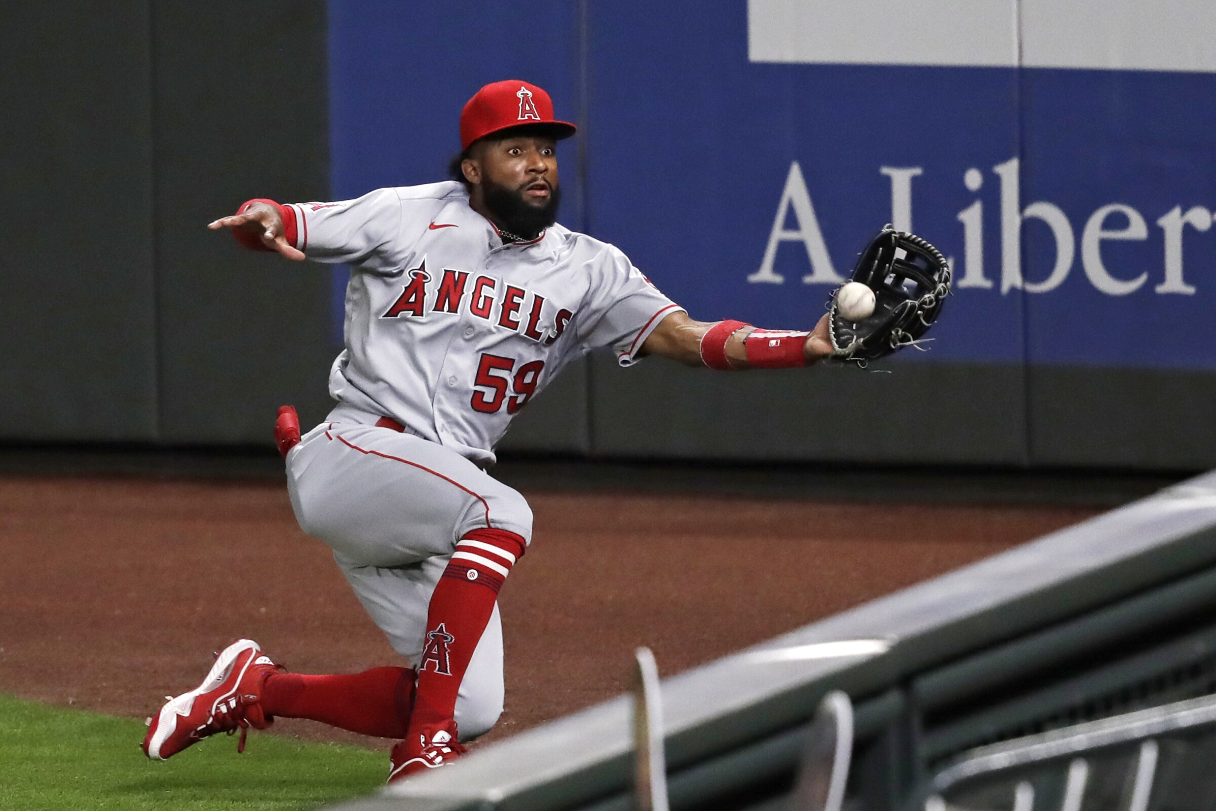 Los Angeles Angels right fielder Jo Adell tries to chase down a deep fly ball.
