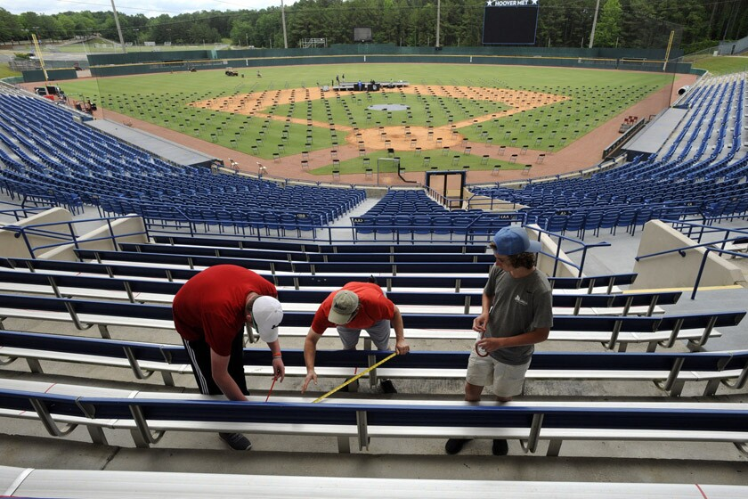 Workers block off seats with red tape May 19 as they prepare for a large high school graduation ceremony in Hoover, Ala.