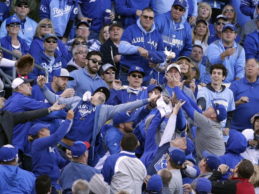 FILE - In this Oct. 17, 2015, file photo, fans reach after a foul ball hit by Toronto Blue Jays' Ben Revere during the third inning in Game 2 of baseball's American League Championship Series against the Kansas City Royals in Kansas City, Mo. The Royals are installing additional netting at Kauffman