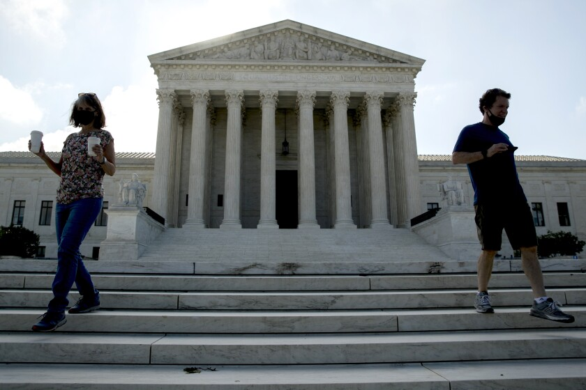 Two people wearing masks walk down the steps outside the Supreme Court.
