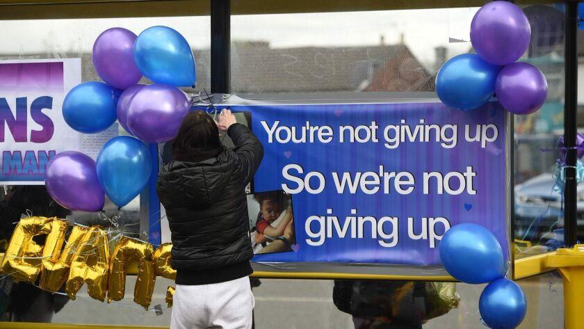 Supporters of Alfie Evans hang balloons at a bus stop opposite Alder Hey Children's Hospital in Liverpool.