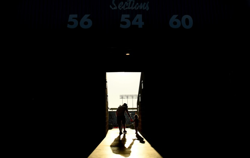 A father takes hold of his son as they walk to their seats at Dodger Stadium. (Wally Skalij / Los Angeles Times)