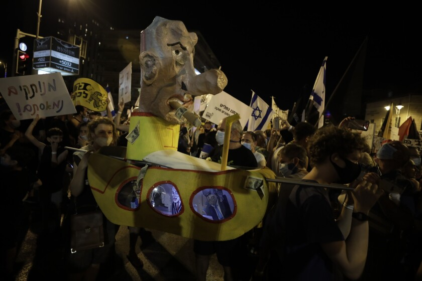 Israelis hold signs and chant slogans during a demonstration against Israeli Prime Minister Benjamin Netanyahu near the Prime Minister's residence in Jerusalem, Saturday, Aug. 15, 2020. (AP Photo/Sebastian Scheiner)