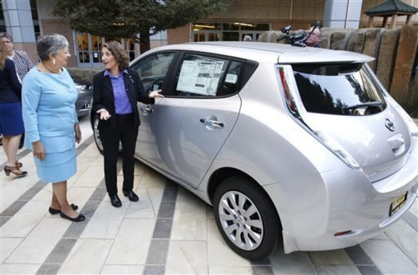 Mary Nichols, chairwoman of the California Air Resources Board, left, and Deb Markowitz, secretary of  the Vermont Agency of  Natural Resources view an electric car displayed in Sacramento, Calif., following a news conference to announce the signing of an agreement on zero emissions cars, Thursday,
