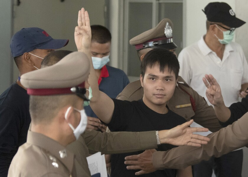 Thai activist Tattep Ruangprapaikitseree gives a three-finger salute as he leaves a police station in Bangkok.