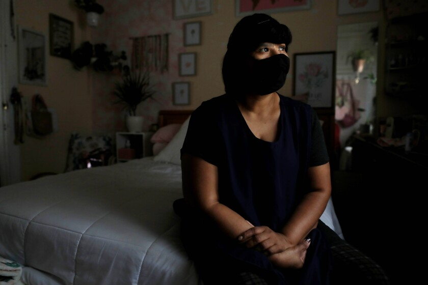 Victoria Galindo Lopez, a pandemic essential worker, sits on her bed with a mask on