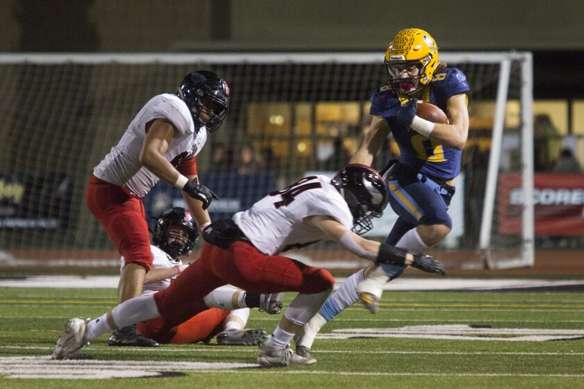 Marina junior Dane Brenton, shown fighting for yardage against La Jolla on Dec. 7, 2019, helped the Vikings win their first league title since 1986.