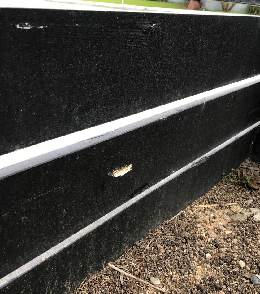 A chip in the wood fence surrounding Mia Elliott's front yard on Lawn Haven Drive marks where she says a bullet hit it during Sunday night's officer-involved shooting in Huntington Beach.