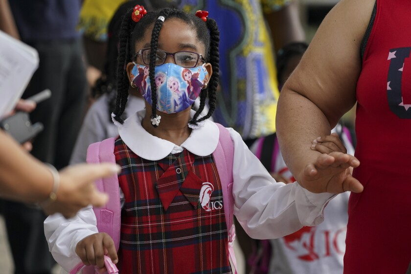 Students wear protective masks as they arrive for classes at the Immaculate Conception School while observing COVID-19 prevention protocols, Wednesday, Sept. 9, 2020, in The Bronx borough of New York. (AP Photo/John Minchillo)