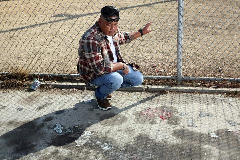 A man kneels on a patch of sidewalk with his hand on a chain-link fence