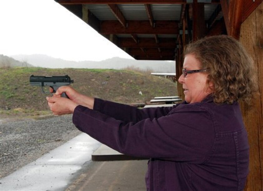 Cynthia Willis shoots her pistol on a firing range March 25, 2011 in White City, Ore. Willis is suing the Jackson County sheriff over denial of a concealed handgun permit after she acknowledged having a medical marijuana card. So far, she has won twice in court, and is waiting for the Oregon Supreme Court to rule. Willis contends that using marijuana for medicine is no different than using any other prescribed drug, and should not preclude her carrying a concealed handgun for personal protection. (AP Photo/Jeff Barnard)