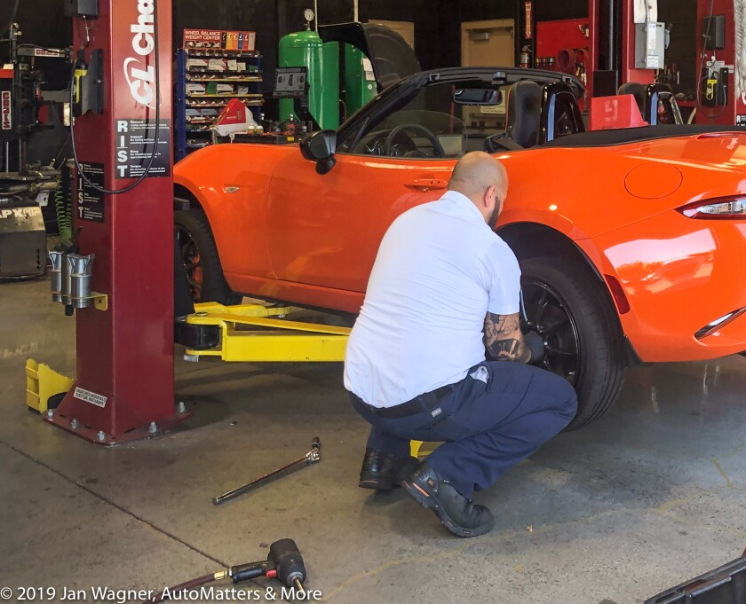 Installing the repaired tire on the car.