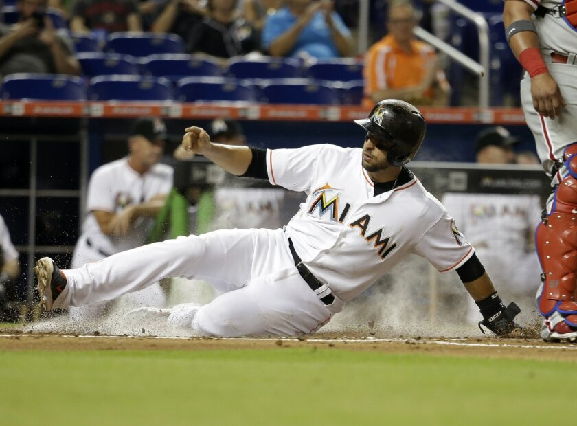 Miami Marlins' Martin Prado scores on a sacrifice fly by Derek Dietrich during the first inning of a baseball game against the Philadelphia Phillies, Thursday, Aug. 20, 2015, in Miami. (AP Photo/Lynne Sladky)
