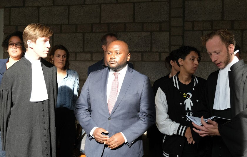 Mpanzu Bamenga, center, stands with his legal team and rights activists outside a courtroom at The Hague District court, Netherlands, Wednesday Sept. 22, 2021, after losing a case. A Dutch court ruled Wednesday that border police can use ethnicity as one of the criteria for selecting people for checks at the border, a legal defeat equal rights activists immediately vowed to appeal. (AP Photo/Mike Corder)